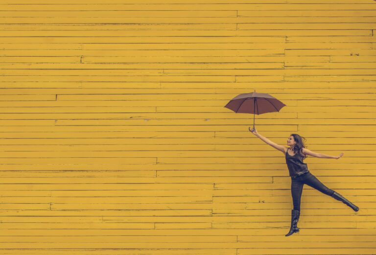 Person with umbrella against yellow wall